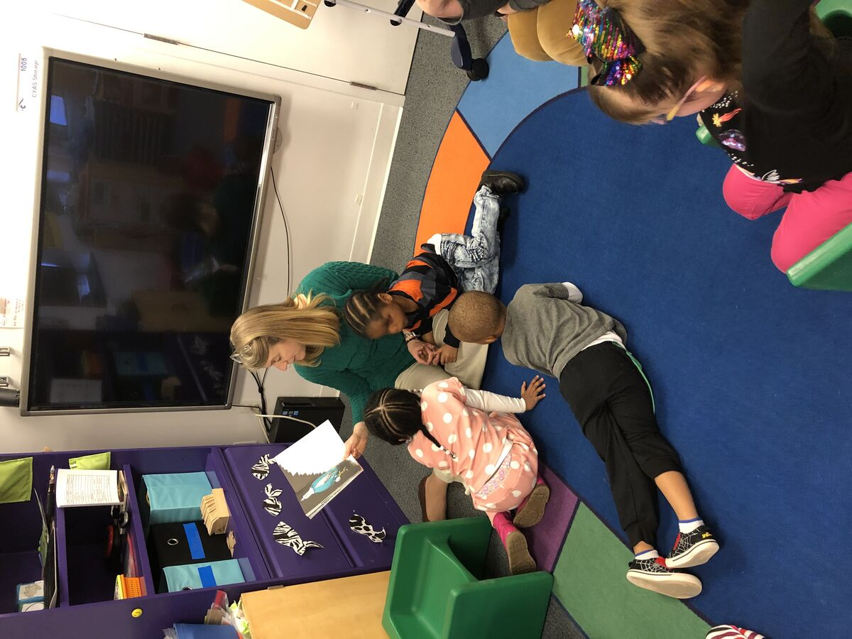 Image of a staff member reading to preschool students