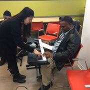 Volunteer helping a client learn to play the keyboard.